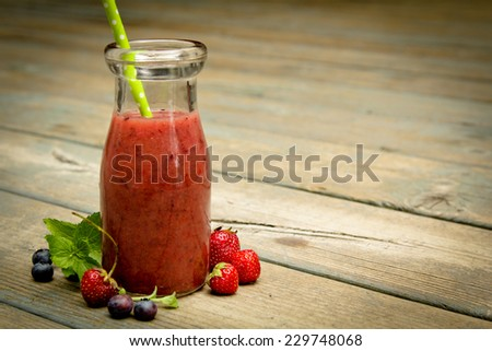 Berry smoothie with fresh fruits on a rustic wood - stock photo
