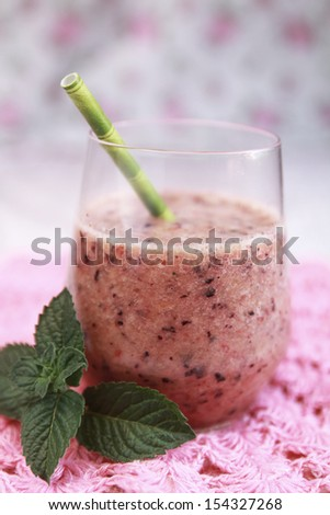 Berry smoothie with green straw on a pink background - stock photo