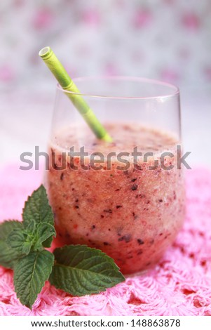 Berry smoothie with mint leave on a pink background - stock photo