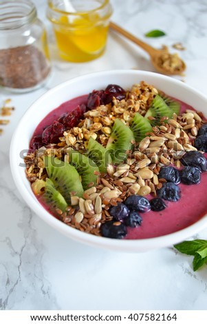 Berry smoothie with yogurt in a bowl for breakfast with blueberries, kiwi, sunflower seeds, granola on a marble background  - stock photo