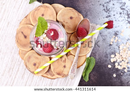 Berry smoothie yogurt with oat flakes and mint leaves for breakfast. Jar with milkshake with raspberries, green straw and silver spoon on the table. Delicious and healthy breakfast - stock photo