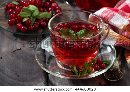 berry tea in cup on wooden table, closeup