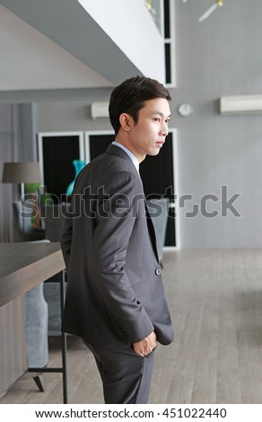 Beside Young businessman standing on workplace in office