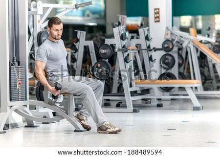 Best body. Smiling athlete bodybuilder man at biceps brachii muscles exercises with training dumbbells in fitness gym. Man looking forward - stock photo