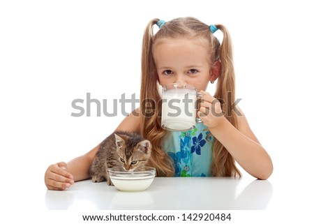 Best buddies drinking milk together - little girl and her kitten - stock photo