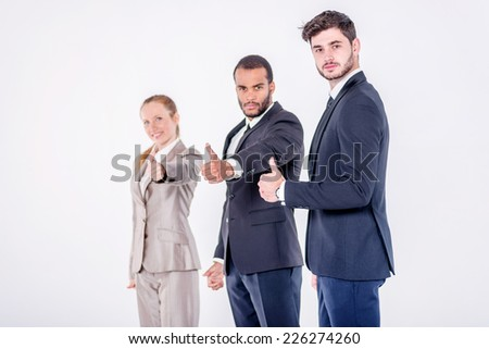 Best business dealings. Three confident and successful businessman standing in a row while businessman showing a thumbs up on a gray background