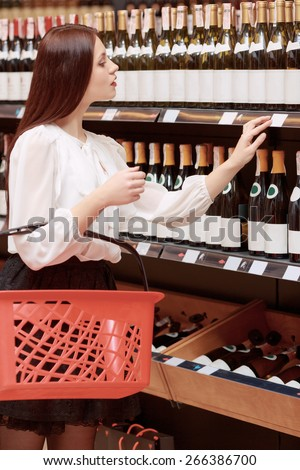 Best choice of wine. Beautiful brunette woman holding a shopping basket chooses wine in liquor store - stock photo