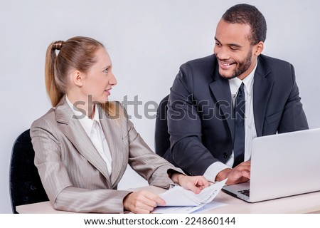Best colleagues. Two smiling businessman looking at each other while businessmen sitting at a table working on a laptop on a gray background. - stock photo