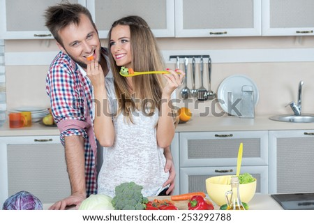 Best cooking food for lovers on the kitchen. Young and beautiful couple in love is preparing food in the kitchen while tasting some food - stock photo