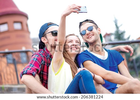 Best day for friendship. Young friends have fun together on the street and smile at each other. Funny guys make Selfie - stock photo