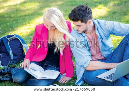 Best day to study. Girl-student and male student holding a laptop and books and look at a textbook while sitting on the grass near the campus of the University at the break. - stock photo