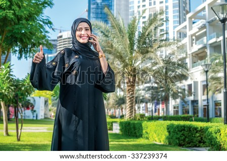 Best deal. Arab businesswoman wearing hijab talking on cell phone against the backdrop of the skyscrapers of Dubai and shows thumb up. The woman is dressed in a black abaya - stock photo