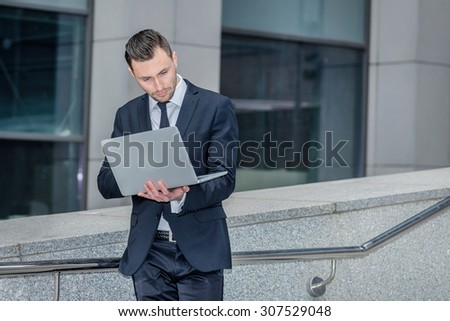 Best employee. Confident businessman coming down the stairs to the street and works at a laptop checking email from a client