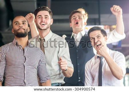 Best fans watching TV and delight football. Four successful men shout and rejoice football meeting. Friends having fun together watching TV - stock photo