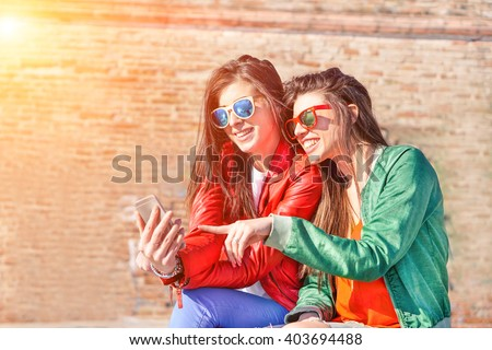 Best fashion addicted friends watching videos surprised on smartphone- Girlfriends having fun outdoors - Technology addiction concept - Main focus on right girl's face with artificial sunlight - stock photo