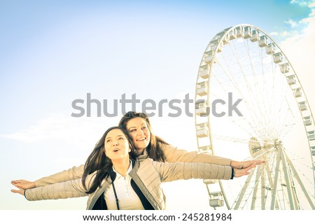 Best female friends enjoying time together outdoors at luna park  - Concept of friendship and happiness with two girlfriends having fun - Happy people at ferris wheel on a bright vintage filtered look - stock photo