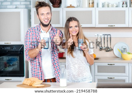 Best food in the morning. Young and beautiful couple in love cuddling in the kitchen and holding a cup of milk while standing in the kitchen and look at the camera with a smile showing thumbs up