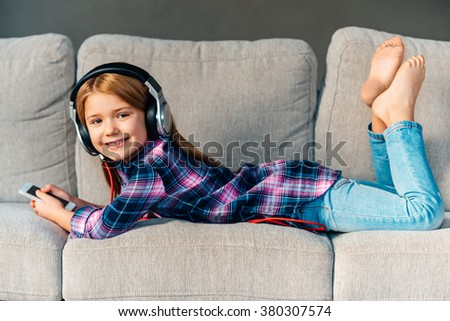 Best free time ever! Beautiful little girl in headphones holding her smart phone and looking at camera with smile while lying on front on the couch at home - stock photo