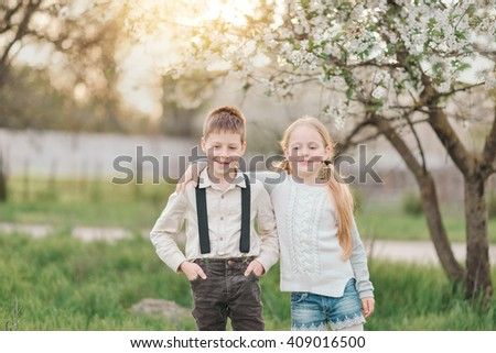best friends a little boy in jeans with suspenders and a blond girl  - stock photo