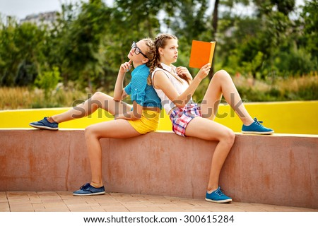 Best friends are reading diary in the summer park. Teen girl dressed in shorts and a shirt. On summer vacation. The concept of true friendship. - stock photo