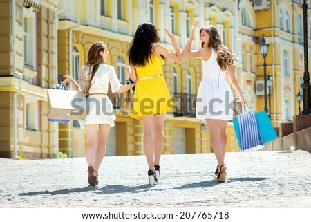 Best friends for shopping. Three attractive young girl holding shopping bags near the shop while walking down the street holding hands view from the back outdoors - stock photo