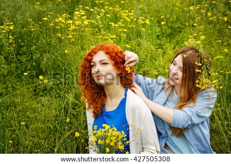 Best friends forever. Friends sitting on the grass in the park. BFF. Close friends. She weaves flower girlfriend hair. - stock photo