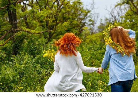 Best friends forever. Girlfriends strolling hand in hand. BFF. Walk. The girl on a head a wreath of wildflowers. Photos from behind. People are not recognizable - stock photo