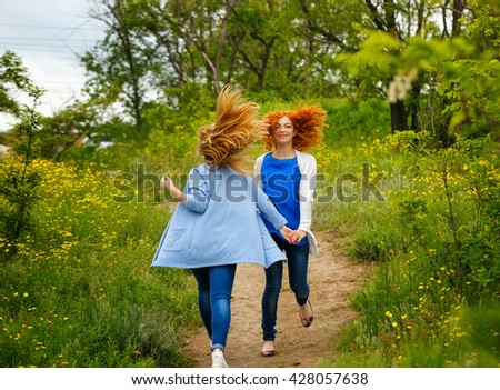 Best friends forever. Girlfriends walking hand in hand in the park. BFF. Close friends. Gentle friendship. Soft focus - stock photo