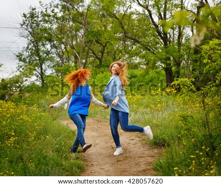 Best friends forever. Girlfriends whirl on the footpath in the park. BFF. Close friends. Gentle friendship. Fooling around together. Soft focus - stock photo