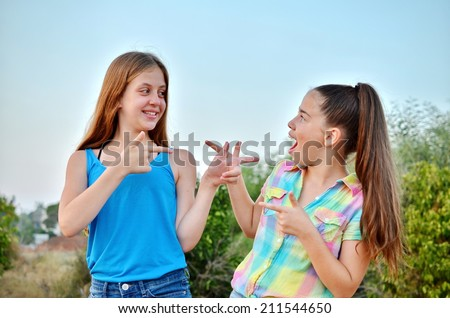 Best Friends Forever - two 12 year old teenage girls looking at each other with a surprised emotion - stock photo
