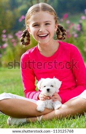 Best friends - happy girl with cute puppy in the garden - stock photo