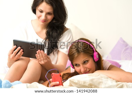 Best friends listening to music and reading in the afternoon - stock photo