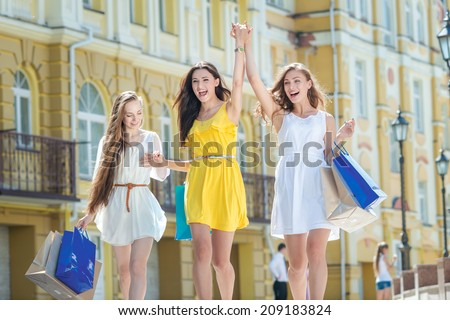 Best friends make a purchase! Girls holding shopping bags and walk around the shops. Smiling girl having fun together - stock photo