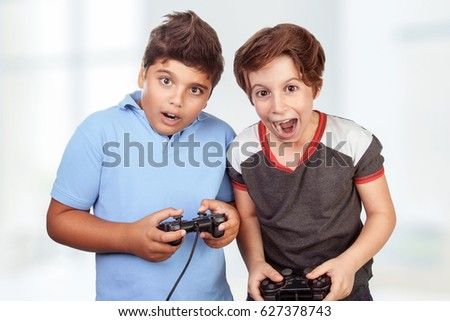 Best friends playing at home, crazy emotion of video games, two excited teen boys enjoying competition, winner and loser in the round