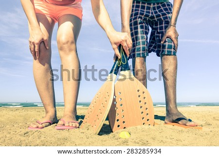 Best friends ready to play beach tennis game at beginning of summer - Concept of multiracial friendship and love - Fun and sport against racism - Vintage filtered look with nostalgic color tones - stock photo