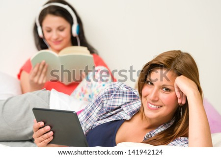 Best friends resting and reading in their room - stock photo
