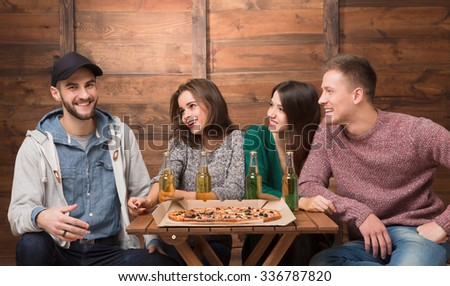 Best friends resting in pizzeria and big excitedly smiling. Three friends looking at their happy friend in cap and waiting for his reaction. - stock photo