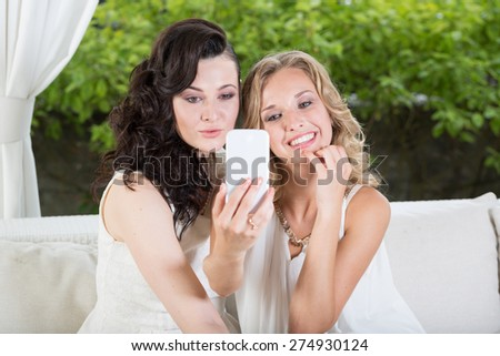 Best friends sitting in the cafe and taking selfie. - stock photo