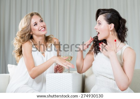 Best friends sitting in the cafe, drinking wine and talking about engagement.  - stock photo