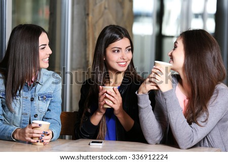 Best friends speaking together  at cafes terrace