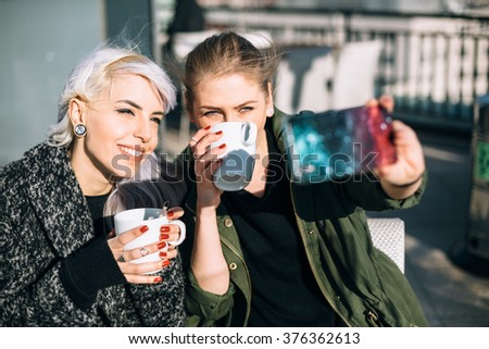 Best friends taking a selfie in coffee shop