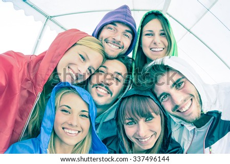 Best friends taking selfie wearing hoodies outdoors - Happy friendship concept with young people looking at camera having fun together - Cold cyan filtered look with focus in the middle of the frame - stock photo