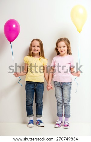 Best friends. Two cute little girls holding balloons on grey background. - stock photo