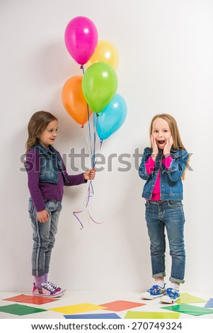 Best friends. Two cute little girls with baloons on colorful background. - stock photo