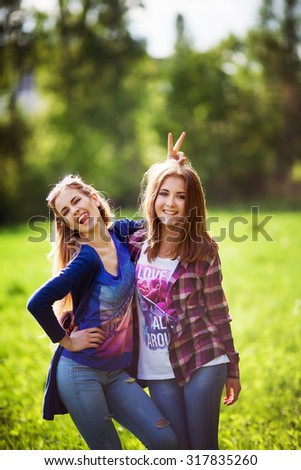 Best friends. Two young woman hug and   laughing  at park - stock photo