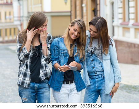 Best friends. Young friends girls are having fun together on the street and looking in the mobile cell phone. Friendship outdoor concept - stock photo