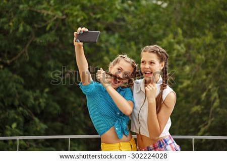 Best girlfriends teenagers being photographed in a summer park. Photo phone selfie. Girls dressed in shorts and a shirt. On summer vacation. The concept of true friendship. - stock photo