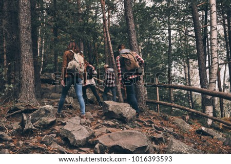 Best hobby ever. Full length rear view of young people in warm clothing moving up while hiking together in the woods