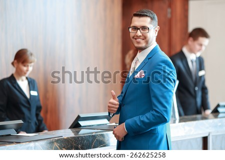 Best hotel service. Good-looking businessman in classical blue suit showing his thumb up reaches the reception desk with two receptionists on the background - stock photo