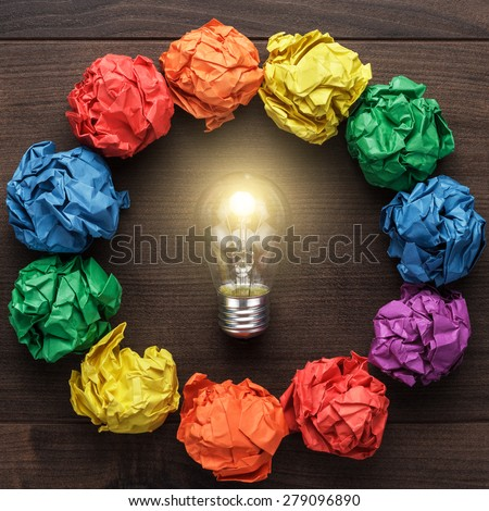 best idea concept with crumpled colorful paper circle and light bulb in the centre on wooden table - stock photo